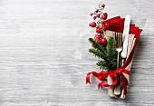 Besteck und Serviette weihnachtlich arrangiert mit Tannen- und Beerenzweig auf grauem Untergrund