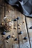 Muesli in a jar with blueberries on wooden table