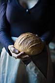 Frau hält frisch gebackenen Brotlaib in den Händen