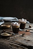Coffee with cream and marshmallow on rustic table