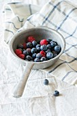 Aluminum colander with fresh raspberries and blueberries