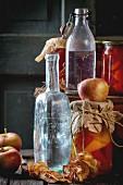 Einmachgläser mit Gemüse (Gurken, Tomaten, Paprika) und frische und getrocknete Äpfel