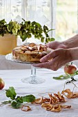Homemade apple pie on glass stand in woman s hands. With baked, fresh and dried apples over table with white tablecloth