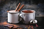 Two vintage mugs with tea and hot chocolate, served with dry tea, rose buds, chopped chocolate and cinnamon sticks