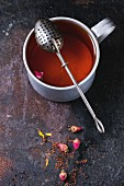 Vintage aluminum mug of hot tea with tea strainer, dry tea and rose buds over dark background