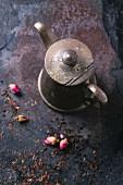 Teeblätter und Rosenknospen vor Vintage-Teekanne aus Metall