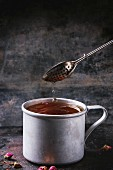 Vintage aluminum mug with flowing hot tea with tea strainer over dark background
