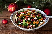 Festive savoy cabbage, roasted sweet potatoes and parsnips salad with Feta cheese, pecans and pomegranate in a bowl