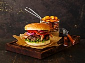 Burger with meat and potato wedges on dark background
