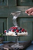 Vintage cake stand with Meringue dessert Pavlova with fresh blackberries and raspberries, strewing by sugar powder