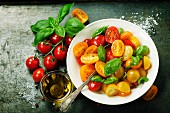 Fresh tomatoes with basil leaves in a bowl on vintage background