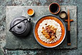 Eel with sauce and sesame on Rice and green tea on stone slate background