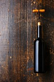 Wine bottle and corkscrew on dark wooden background