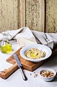 Hummus (Kichererbsencreme, Orient) mit Olivenöl und Brot auf Holzbrett