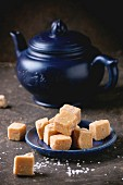 Blue ceramic plate with fudge candy ceramic teapot, served with sugar cubes over dark background