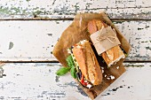 Two half of vegetarian baguette submarine sandwich with grilled eggplant, pepper and feta cheese served on baking paper
