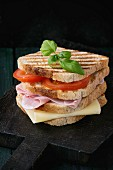 Whole grain grilled sandwich bread with ham, cheese and tomatoes on black wooden chopping board