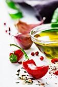 Stillleben mit Chilischoten, Knoblauch, Kräutern, Gewürzen und Öl im Schälchen