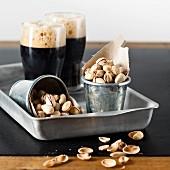 Pistazien in Metallbechern und zwei Glas dunkles Bier
