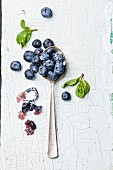 Ripe blueberries in spoon on textured background