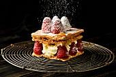 Millefeuille Dessert mit Himbeeren vor schwarzem Hintergrund