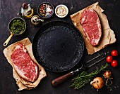 Raw fresh meat Striploin steaks with ingredients around frying pan on dark background