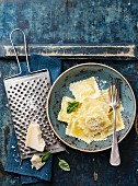 Ravioli pasta with mozzarella cheese, basil and parmesan on blue background