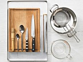 Various kitchen utensils: pot, sieve, baking tray, pastry brush, spoons, knives