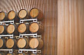 Wooden casks stacked up in front of a wooden wall