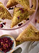 Pistachio baklava with rose petals on cake stand with pink napkin