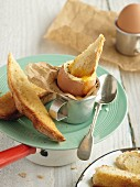 Boiled egg and soldiers on vintage plate with silver spoon