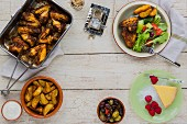 Summer lunch of chicken wings, potato wedges, olives and salad with lemon tart and fresh raspberries for dessert