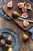 Sliced figs on a chopping board with knife and a plate of whole figs