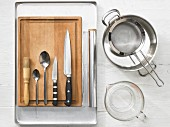 Various kitchen utensils: pot, sieve, oven tray, pastry brush, spoons, knives