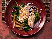 Chicken breast with a cashew nut crust on spicy vegetables