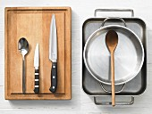 Various kitchen utensils: oven dish, pot, spoon, knife