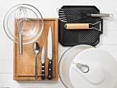 Verschiedene Küchenutensilien: Salatschleuder, Grillpfanne, Pfannenwender, Messer, Schneebesen