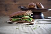 Veganes Zwiebel-Walnuss-Baguette, belegt mit Salat, Räuchertofu, Salatgurke und Kresse