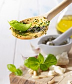 A wooden spoon with pesto and a basil leaf