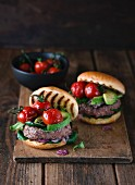 Homemade burgers with avocado and cherry tomatoes on a wooden board