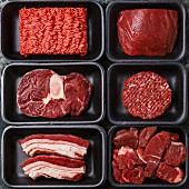 Verschiedene rohe Fleischwaren in Plastikschalen (Aufsicht)
