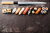 Sushi rolls and nigiri with Japanese knife on stone slate background