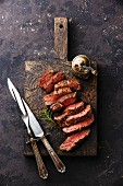 Medium gebratenes Rindersteak in Scheiben geschnitten mit Fleischbesteck auf Holzbrett