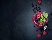 Beeren-Smoothie in Henkelglas auf schwarzem Untergrund