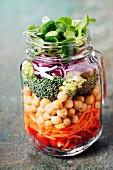 Frische Zutaten für Gemüsesalat mit Kichererbsen in Einmachglas geschichtet