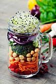 Zutaten für Gemüsesalat mit Kichererbsen und Sprossen in Henkelglas geschichtet