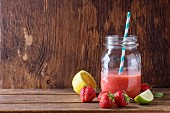 Glass jar with red strawberry smoothie, served with fresh strawberries, lemon and lime over wooden table