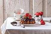 Homemade chocolate cake with strawberries and dark chocolate ganache, served on vintage plate