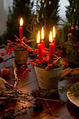 Tontöpfchen gefüllt mit Moos, Kerzen und Ilexzweigen, befestigt mit Drahthaken