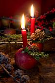 Apfel mit Kerze und Lärchenzweig als Weihnachtsdeko